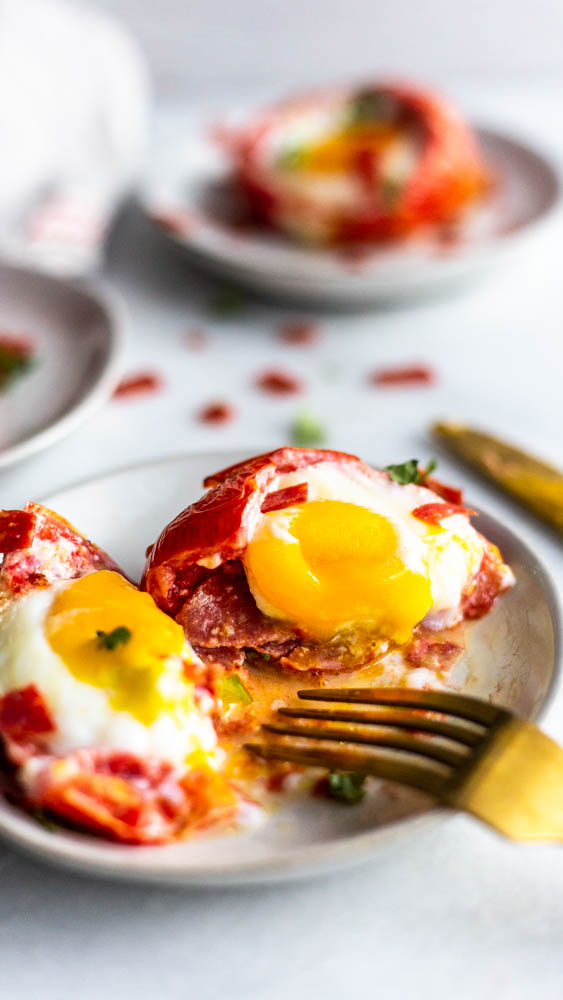 These Pizza Baked Eggs are a super simple breakfast idea. Stuff a tomato with pepperoni and an egg and bake for a gluten and dairy free life hack.