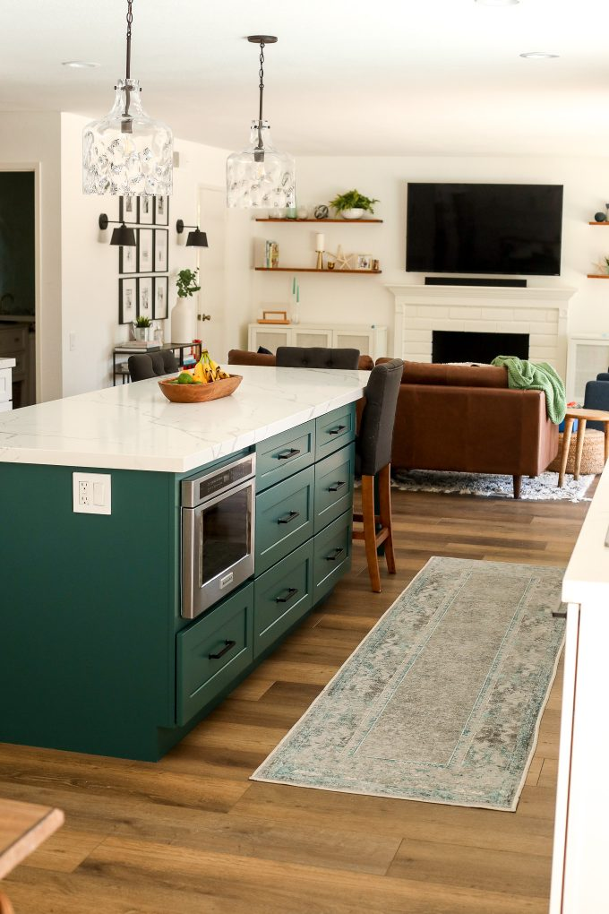2020 Kitchen Remodel with a green island and surrounding white cabinets.